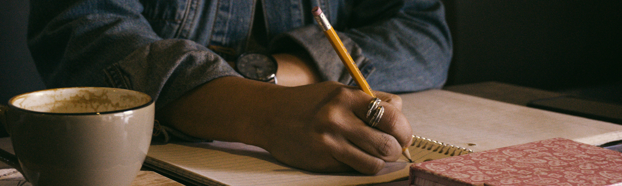 Person writing in a notebook. Photo by Kat Stokes on Unsplash