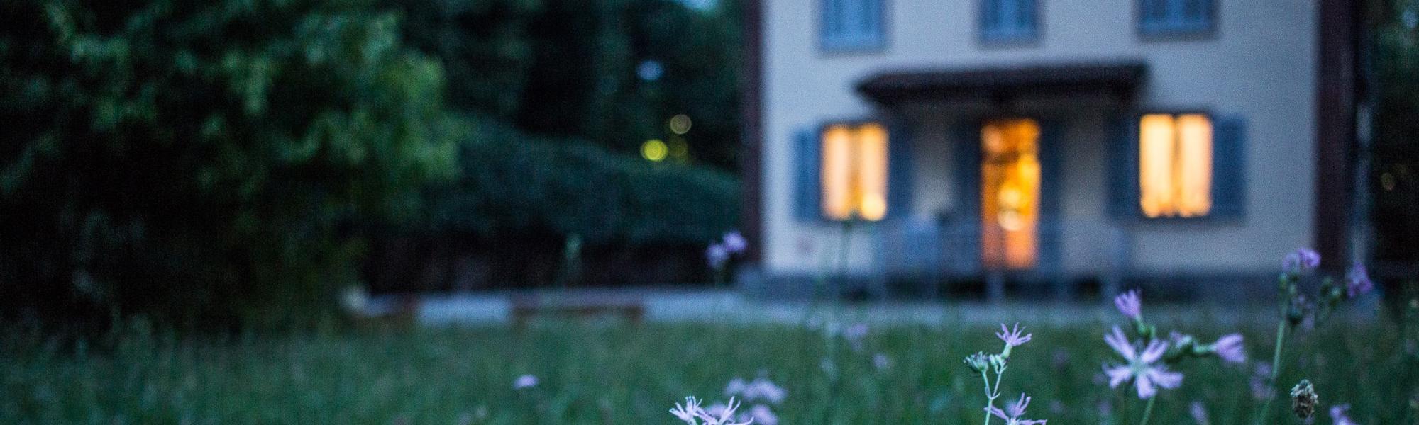 House at dusk with lights at the wondows. Photo by Valentina Locatelli on Unsplash