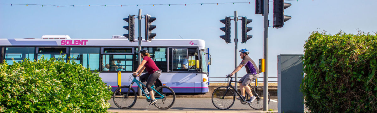 Two cyclists on a seafront road, with a single-decker bus on the other side of the road