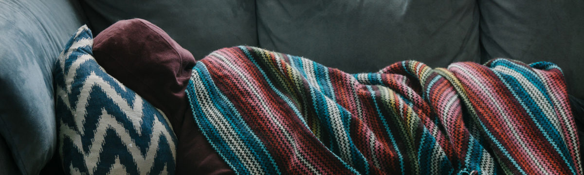 Young man asleep on sofa with blanket and hood. Photo by Rex Pickar on Unsplash