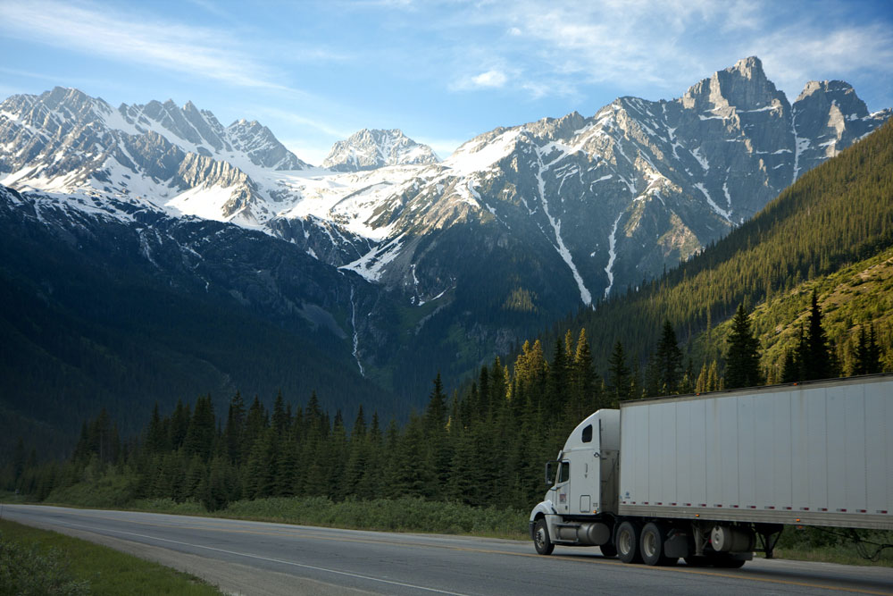 Large articualted truck on a highway amongst snow-capped mountains and conifer forest